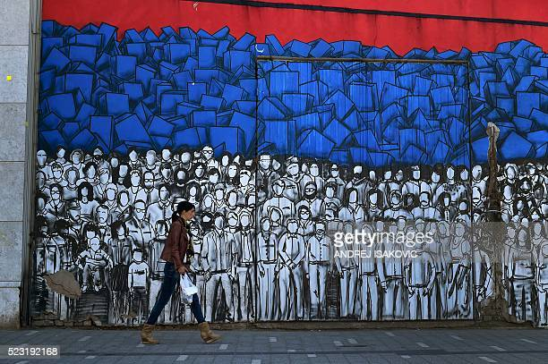 A woman walks past a mural depicting many famous Serbs and the Serbian national flag in Belgrade on April 22 2016 Serbian Prime Minister Aleksandar...