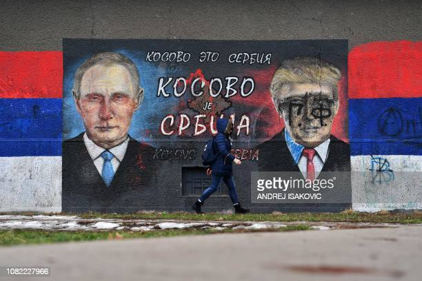 A woman walks past a mural depicting Russian President Vladimir Putin and US President Donald Trump and bearing Cyrillic writing reading Kosovo is...