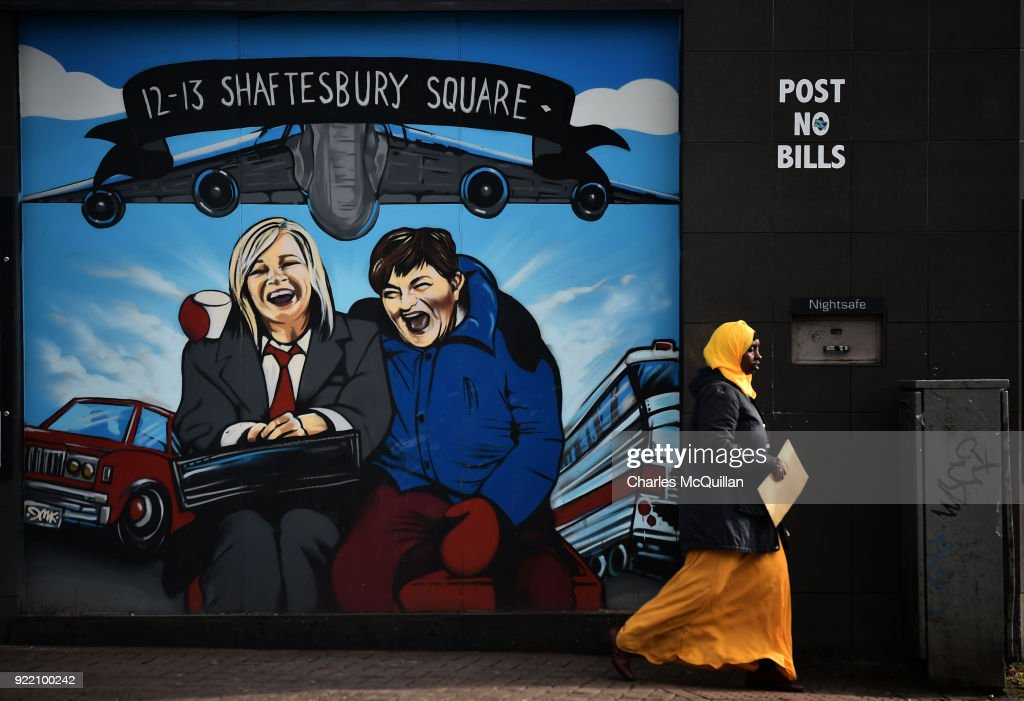 A woman walks past a mural depicting Sinn Fein vice president Michelle O'Neill (L) and DUP leader Arlene Foster as the unlikely bedfellow characters from the movie Planes, Trains and Automobiles on February 21, 2018 in Belfast, Northern Ireland. Talks to restore the Northern Ireland power sharing executive collapsed last week with the main sticking point being a proposed Irish language act. A leaked draft agreement between Sinn Fein and the DUP confirmed a three-stranded approach to the language question, which would have resulted in an Irish language act, an Ulster-Scots act and a so-called respecting language and diversity act. The province has been without a government for over 13 months since then deputy First Minister Martin McGuinness resigned his position in protest at a botched renewable heating scheme.