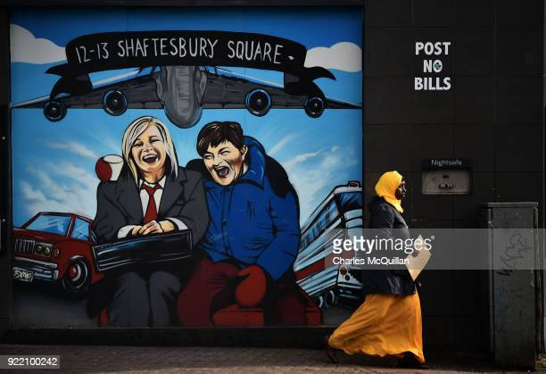 Woman walks past a mural depicting Sinn Fein vice president Michelle O'Neill and DUP leader Arlene Foster as the unlikely bedfellow characters from...