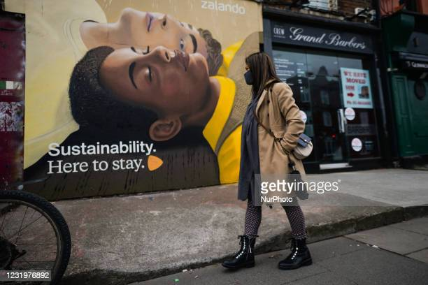 Woman walks past a mural for the Zalandos spring marketing campaign 'Here to Stay'. The campaign aims to foster a dialogue around core values, such...