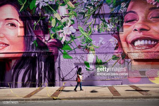 Woman walks past a mural in the Charles Village neighborhood on October 14 in Baltimore, Maryland. - Demon Lane says his east Baltimore neighborhood...