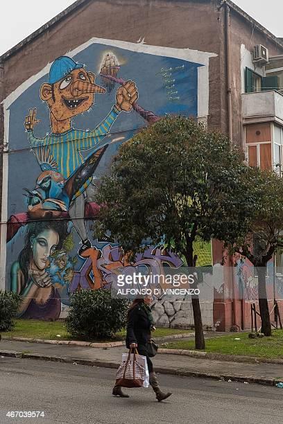 IDE A woman walks past a mural in the Tamburi district near the Ilva steel plant on March 18 2015 in Taranto The site in Taranto in the Puglia region...
