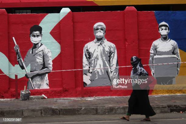 A woman walks past a mural in tribute to frontline workers during the COVID19 pandemic in Mumbai India on June 15 2020 India has begun gradually...