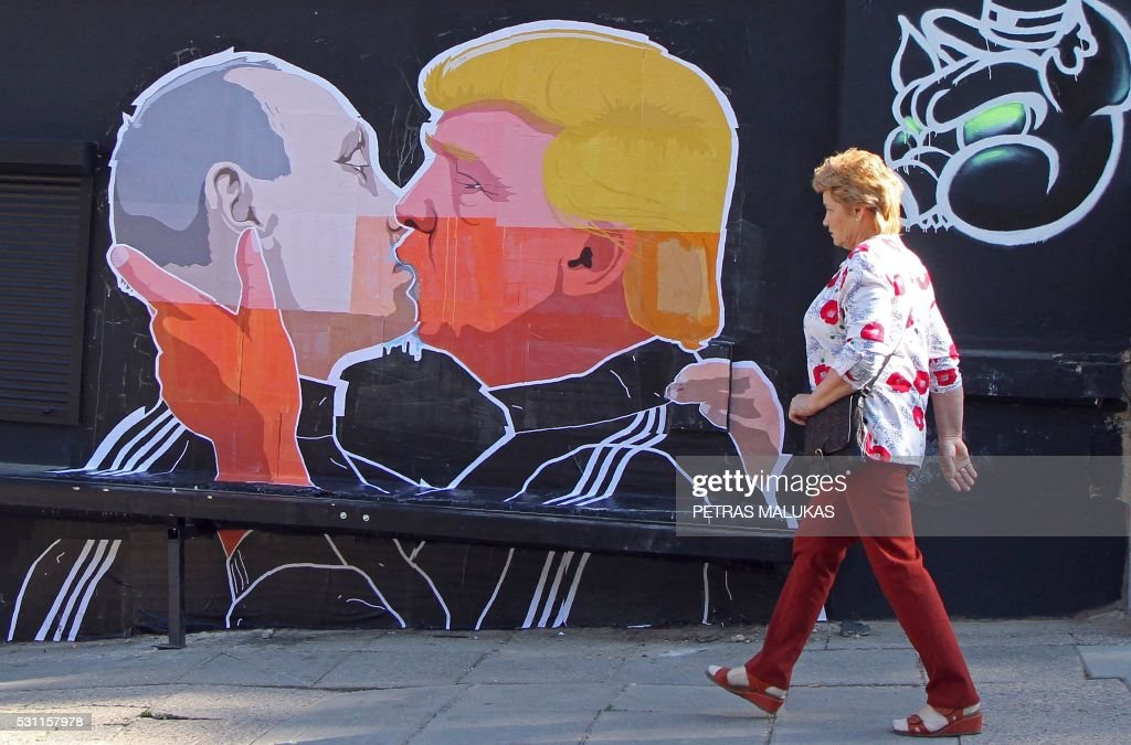 A woman walks past a mural on a restaurant wall depicting US Presidential hopeful Donald Trump and Russian President Vladimir Putin greeting each other with a kiss in the Lithuanian capital Vilnius on May 13, 2016. Kestutis Girnius, associate professor of the Institute of International Relations and Political Science in Vilnius university, told AFP -This graffiti expresses the fear of some Lithuanians that Donald Trump is likely to kowtow to Vladimir Putin and be indifferent to Lithuanias security concerns. Trump has notoriously stated that Putin is a strong leader, and that NATO is obsolete and expensive. / AFP / Petras Malukas