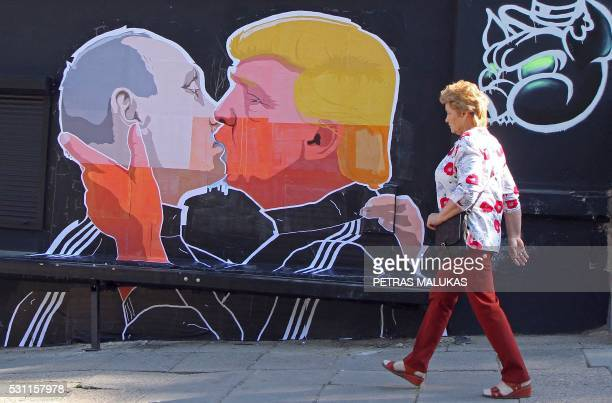 A woman walks past a mural on a restaurant wall depicting US Presidential hopeful Donald Trump and Russian President Vladimir Putin greeting each...