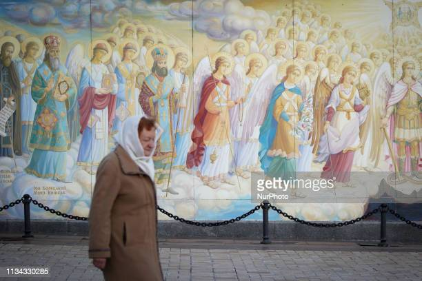 A woman walks past a mural outside Saint Michael's GoldenDomed Monastery in Kyiv Ukraine on April 1 2019