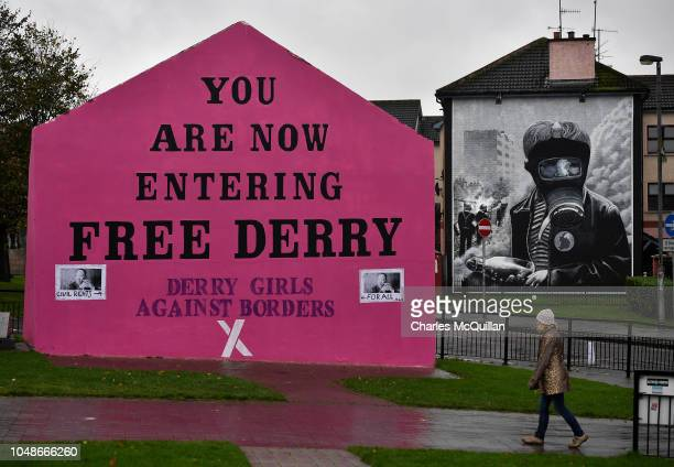 Woman walks past a mural that states 'Derry Girls Against Borders' at Free Derry Corner on October 9, 2018 in Londonderry, Northern Ireland. Talks on...