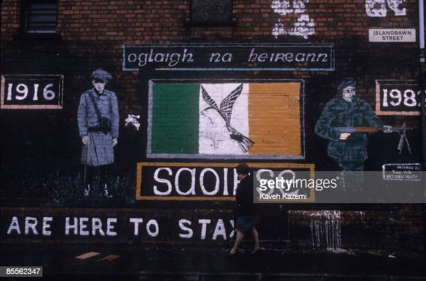 A woman walks past a mural which depicts the armed struggle of the Republican movement on Islandbawn Street in west Belfast 15th September 1985 The...