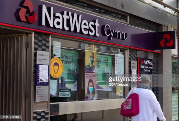Woman walks past a NatWest bank in Wales, UK. Eight more people have died with coronavirus in Wales and the overall infection rate has risen slightly.