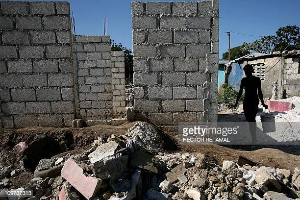 Woman walks past a newly built wall on January 5, 2011 in Port-au-Prince. One year after Haiti's earthquake, only five percent of the rubble has been...