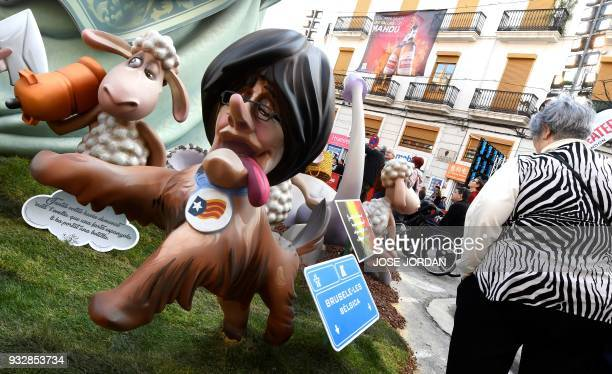 A woman walks past a Ninot of the Falla del Pilar depicting Catalonia's deposed leader Carles Puigdemont during the Fallas Festival in Valencia on...