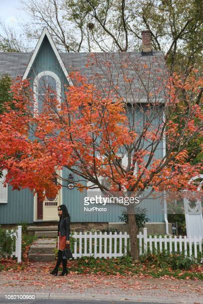 Woman walks past a old house during the Autumn season in Unionville, Ontario, Canada