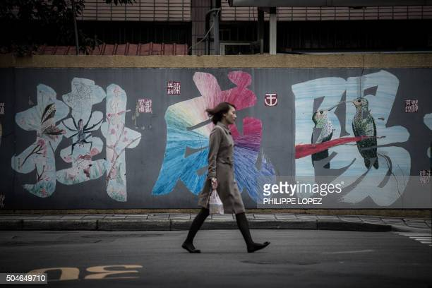 TOPSHOT A woman walks past a painted wall in Taipei on January 12 2016 Taiwan's voters angry at low salaries and unaffordable housing are set to...