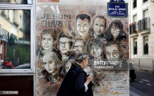 Woman walks past a painting by French street artist and painter Christian Guemy, known as C215, in tribute to members of Charlie Hebdo newspaper who...