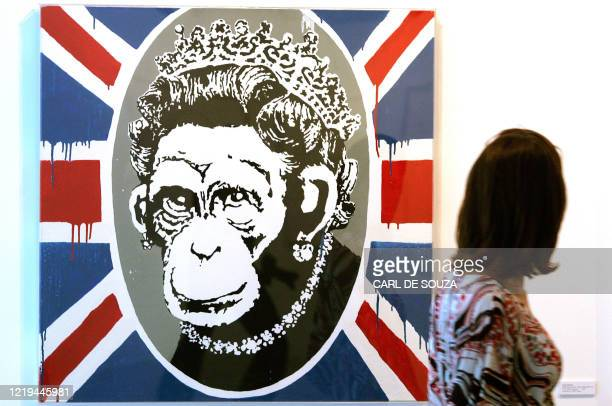 A woman walks past a painting by Modern artist Banksy entitled Deride and Conquer painted in 2002 during an exhibition in London 09 August 2007 An...