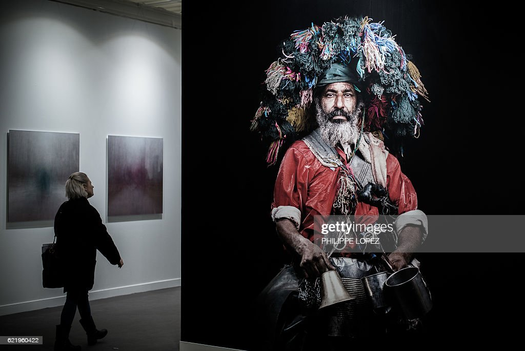 A woman walks past a photograph by late French-Moroccan photographer Leila Alaoui during the opening of the 20th edition of Paris photo, the international fine art photography fair at the Grand Palais in Paris on November 9, 2016. The fair runs from November 10 to 13, 2016. / AFP / PHILIPPE
