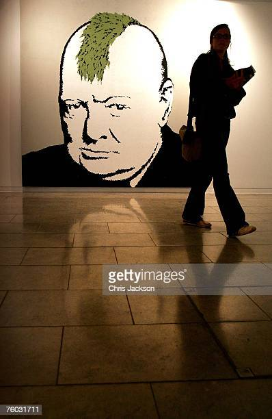 A woman walks past a picture of Winston Churchill by Banksy at the Warhol vs Banksy Exhibition on August 9 2007 in London England