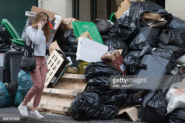 A woman walks past a pile of uncollected rubbish on June 10 2016 in Paris Paris Mayor Anne Hidalgo promised on June 10 2016 that 'all rubbish' piling...