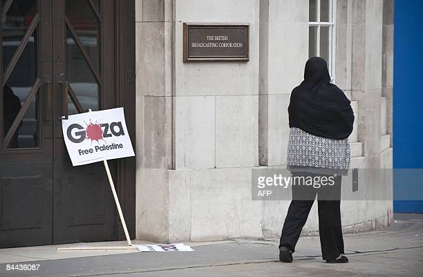 A woman walks past a placard during a demonstration outside the BBC office in London on January 24 2009 Protesters gathered in a rally against the...