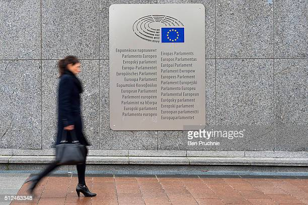 A woman walks past a placard with the words European Parliament inscribed in several languages of the European Union member states outside the Espace...