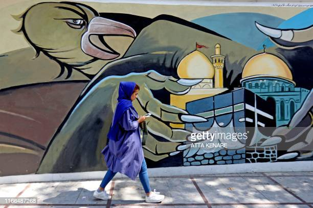 A woman walks past a political mural at Palestine Square in the Iranian capital Tehran on September 7 2019 Iran said Saturday it has fired up...