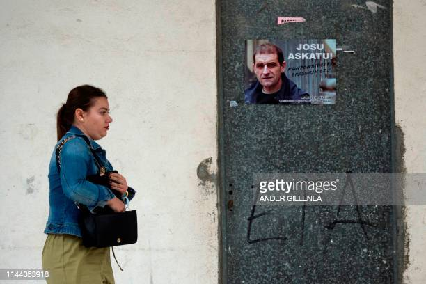 A woman walks past a poster calling for the release of one of the most influential leaders of former Basque separatist group ETA Jose Antonio...
