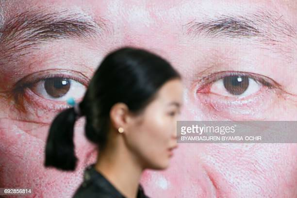 A woman walks past a poster for Mongolian People's Party candidate Mieygombo Enkhbold near a campaign event marking the opening of campaigning for...