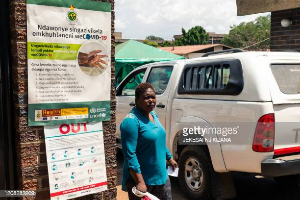 Woman walks past a poster illustrating good hygiene practices to combat the COVID-19 coronavirus as the Zimbabwe Hospital Doctors Association vowed...