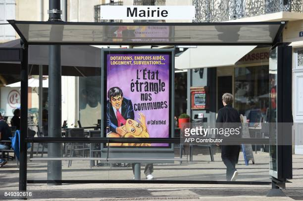 A woman walks past a poster in Beziers on September 19 2017 depicting a man strangling a woman and reading endowments job help housing subsidiesthe...