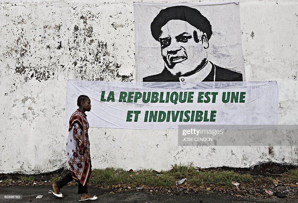 A woman walks past a poster of Comoran P : News Photo