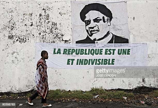 A woman walks past a poster of Comoran President Ahmed Abdallah Sambi which reads the Republic is one and indivisible in Moroni capital of Grand...