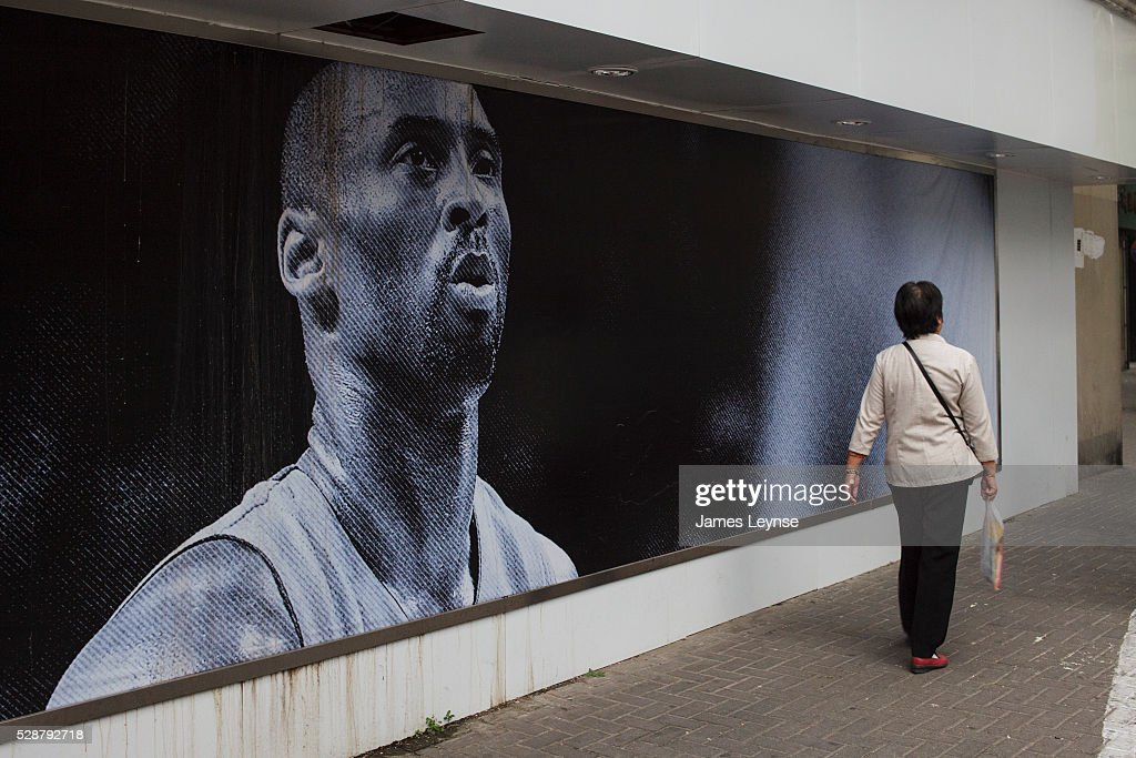 A Woman Walks Past Poster Of Kobe Bryant Outside Nike Store In Shanghai