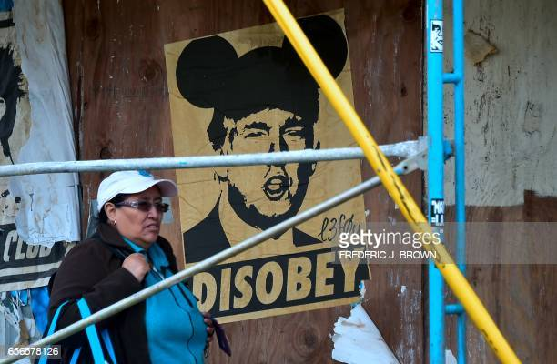 A woman walks past a poster of of US President Donald Trump depicted with Mickey Mouse ears in Los Angeles California on March 22 2017 According to a...