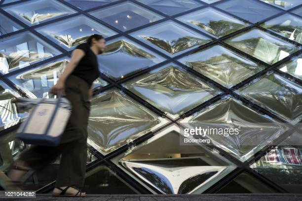 A woman walks past a Prada SpA store in the Omotesando area of Tokyo Japan on Tuesday Aug 21 2018 Japan is scheduled to release February's Consumer...