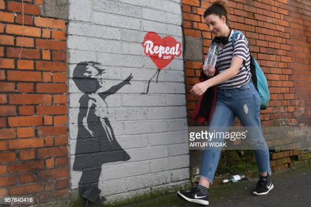 A woman walks past a prochoice mural based on a work by Banksy urging a yes vote in the referendum to repeal the eighth amendment of the Irish...