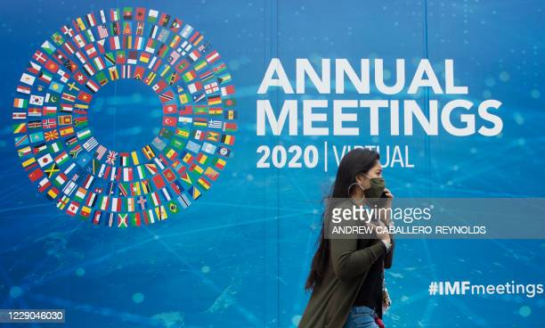 Woman walks past a promotional poster for the virtual 2020 Annual Meetings outside the International Monetary Fund at their headquarters in...