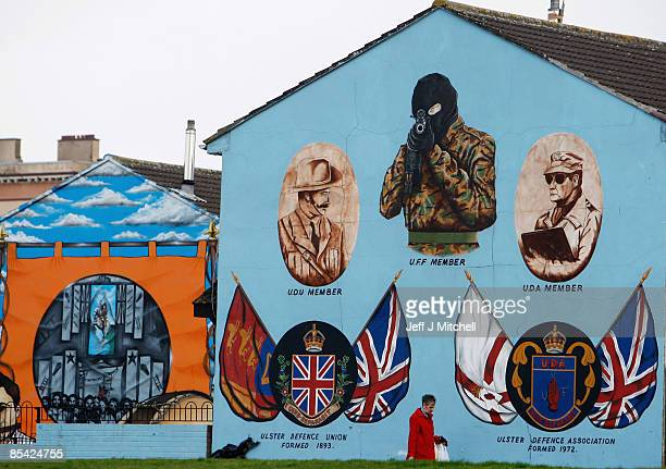 A woman walks past a protestant loyalist mural in the Shankhill area of Belfast on March 14 2009 in Northern Ireland Communities in Northern Ireland...