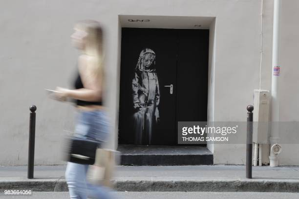 A woman walks past a recent artwork by street artist Banksy in Paris on June 25 on a side street to the Bataclan concert hall where a terrorist...