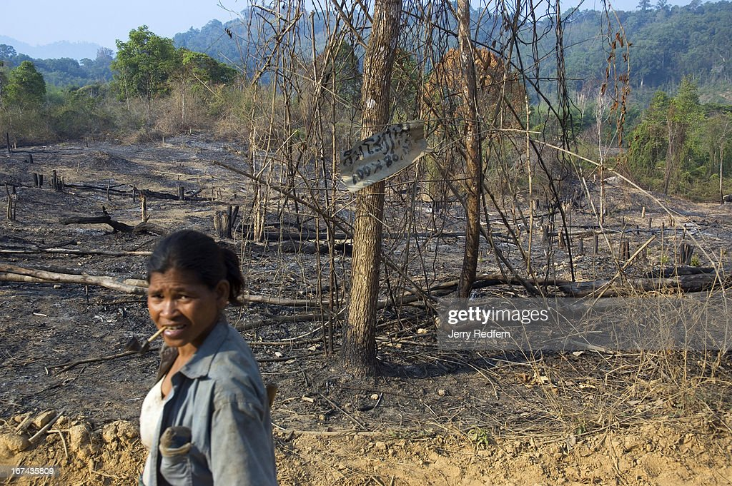 A woman walks past a recently cleared field. Burning fields in the area often 'cook off' buried UXO (unexploded ordnance) shooting shrapnel up to a mile away. Etoum lies on a crossroads of the old Ho Chi Minh Trail and was heavily bombed during the Vietnam War. The Lao government moved Etoum from a nearby location to its current spot atop the heavily bombed patch of ground two years ago. Locals now must contend with UXO throughout their new village and farmland. Locals also search for UXO to sell to the scrap trade. Though very dangerous, selling war scrap pays better than farming in the area..