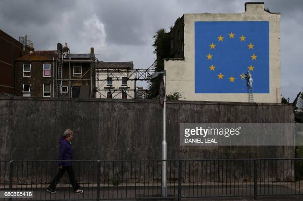 A woman walks past a recently painted mural by British graffiti artist Banksy depicting a workman chipping away at one of the stars on a European...