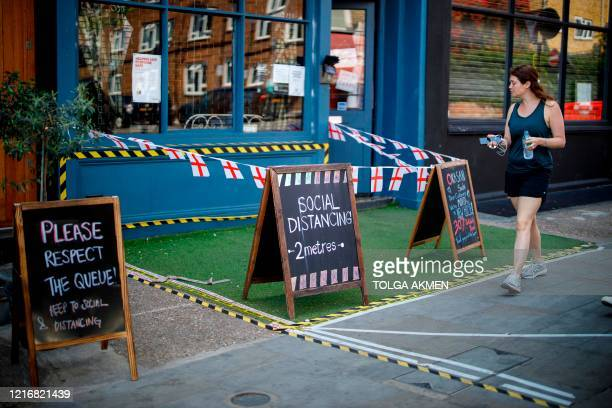 Woman walks past a restaurant with social distancing markings in Portobello Market in west London on June 1 following the easing of the lockdown...
