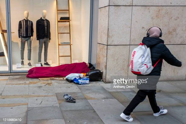 A woman walks past a rough sleeper in central Manchester on March 30 2020 in Manchester United Kingdom The Coronavirus pandemic has spread to many...