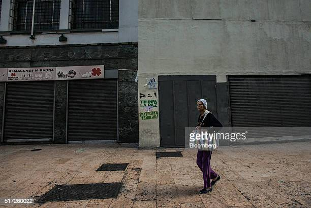 A woman walks past a row of closed stores in the usually busy downtown shopping district in Caracas Venezuela on Tuesday March 22 2016 Venezuela shut...