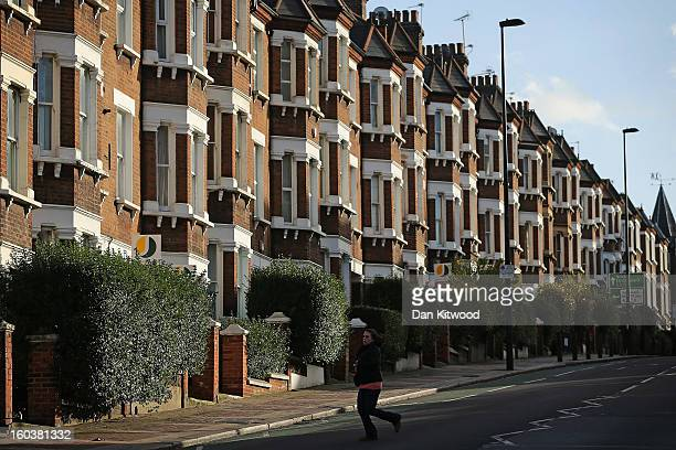 A woman walks past a row of houses near Battersea on January 30 2013 in London England According to a report from independent analysts Oxford...