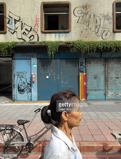 A woman walks past a rundown building covered with graffiti in Taipei on September 11 2008 Taiwan announced an economic stimulus package worth 56...