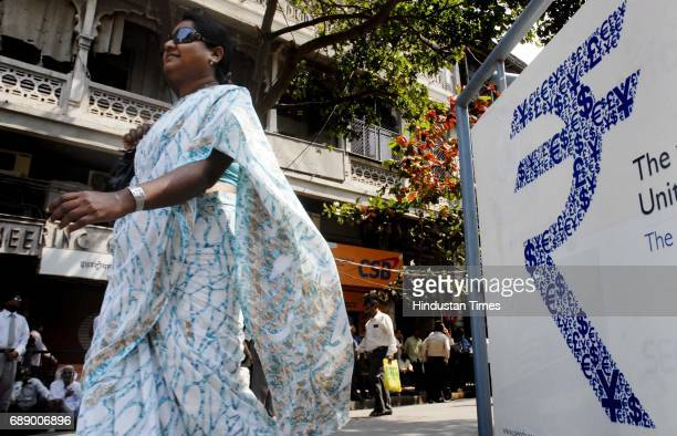 Woman walks past a Rupee symbol as Budget 2011 is announced at BSE Dalal Street Morning