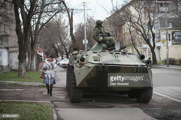 A woman walks past a Russian military personnel carrier outside a Ukrainian military base on March 18 2014 in Simferopol Ukraine Voters on the...