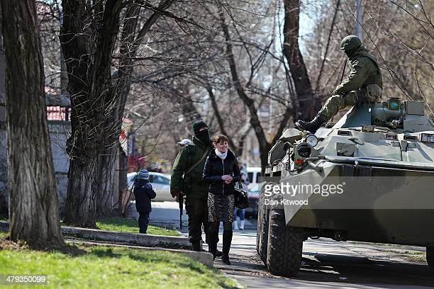 Woman walks past a Russian military personnel carrier outside a Ukrainian military base on March 18, 2014 in Simferopol, Ukraine. Voters on the...