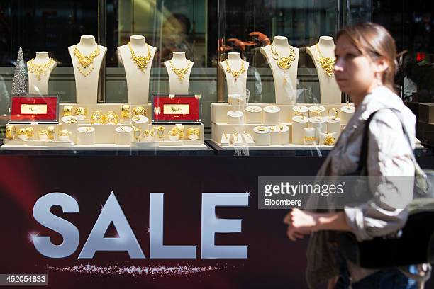 A woman walks past a sale sign displayed below gold jewelry in the window of a Chow Tai Fook Jewellery Group Ltd store in the shopping district of...